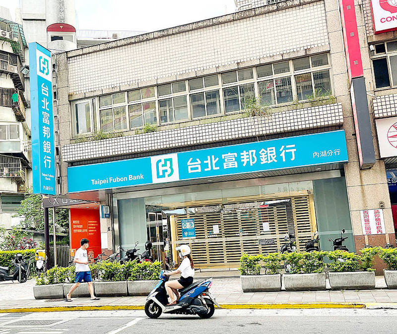 A person rides a scooter past a Taipei Fubon Bank branch in Taipei's Neihu District on May 9. More financial companies have allowed their employees to work from home to contain the domestic spread of COVID-19, the Financial Supervisory Commission said. Photo: CNA