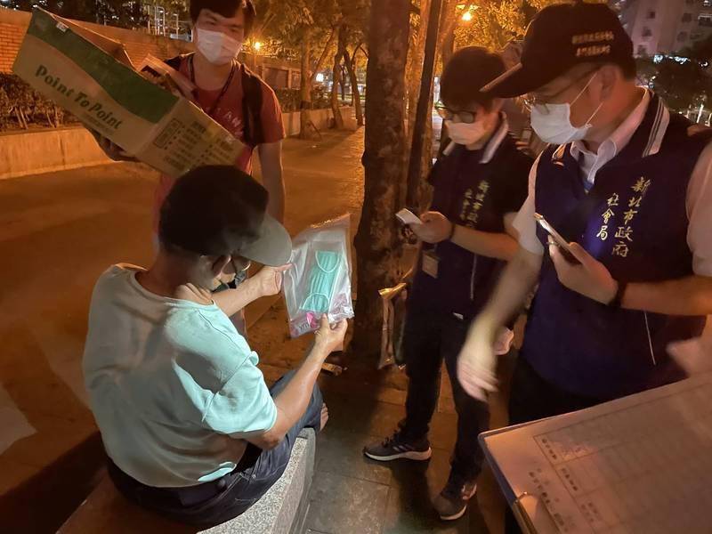 社會局人員致贈街友含口罩的防疫包。(社會局提供)