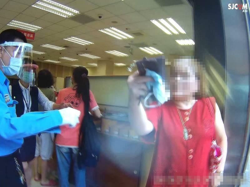 陳姓婦人今天上午因未戴口罩,被銀行保全阻擋在外,不得其門而入。(記者林嘉東翻攝)