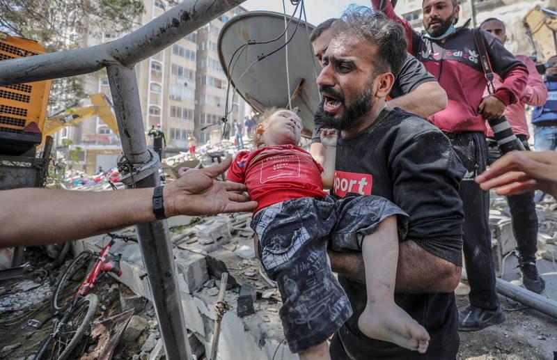 以色列持續對加薩進行空襲,造成當地無數死傷。圖為一名巴勒斯坦父親從被炸毀的房屋裡抱出死去的孩童。(歐新社)