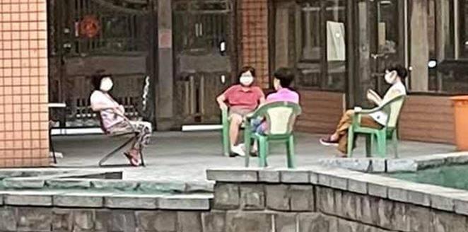 網友拍照社區內的4名阿姨想聊天又想要有社交距離,搬了椅子在室外排成梅花座「開槓」。(圖取自路上觀察學院)