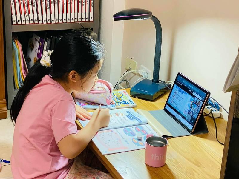 第一次停課不停學,花蓮小朋友第一天的在家學習一邊看電腦一邊寫功課,家長在旁監督。(圖由讀者吳宛霖提供)