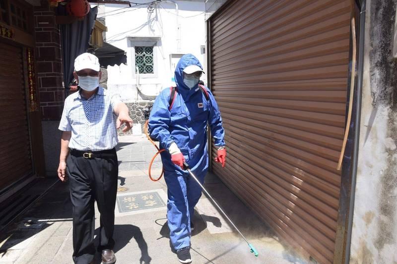 澎湖縣長賴峰偉陪同消毒人員,沿街消毒清理環境。(澎湖縣政府提供)