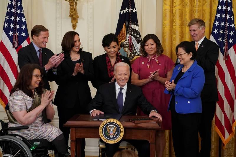 美國總統拜登(Joe Biden)20日在多位亞裔國會議員的見證下簽署「新冠病毒仇恨犯罪法案」(Covid-19 Hate Crimes Act)。(路透)