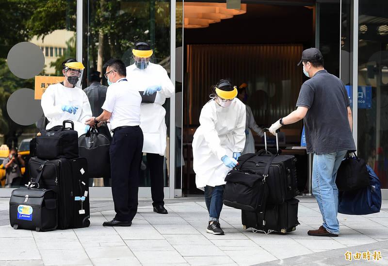 華航諾富特飯店二館22日重啟營運,專責為機組人員專責檢疫處所,入住需要被隔離檢疫的機組員,穿著隔離衣的工作人員在大門口為準備入住的機組員的行李噴灑酒精消毒。 (記者朱沛雄攝)