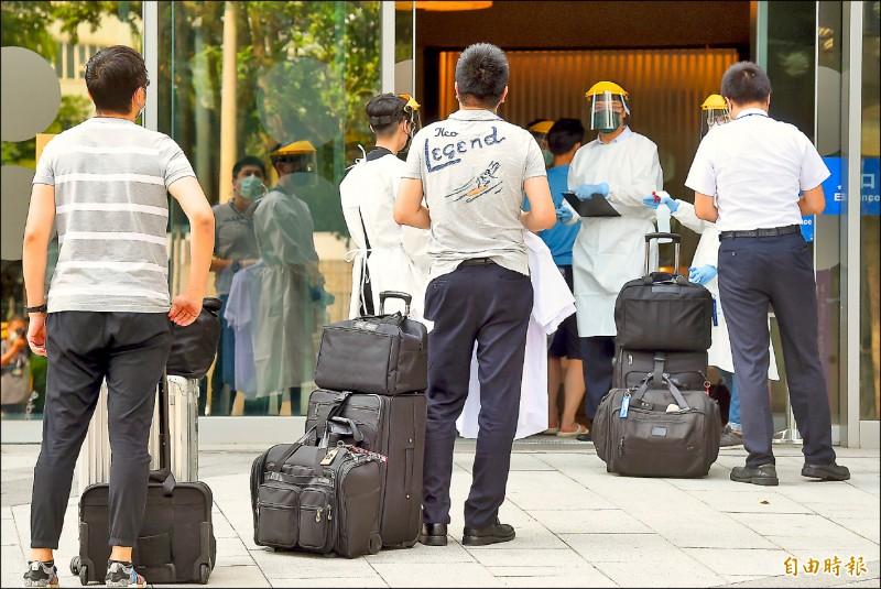 華航諾富特飯店二館22日重啟營運,轉型為機組人員專責檢疫處所,準備入住機組員排隊等候消毒。 (記者朱沛雄攝)