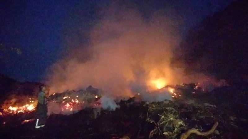 新竹縣關西鎮仁安里一處私人專堆廢樹頭樹枝的堆置場大火,從白天燒進黑夜,迄今仍不熄。(圖由徐瑜新提供)