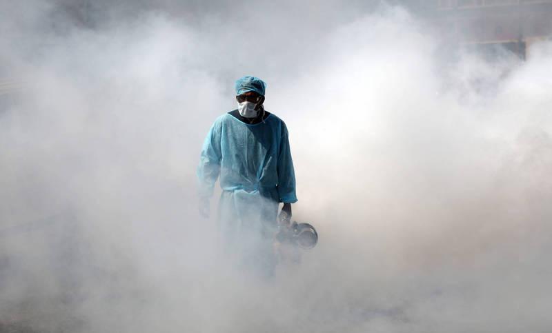 去年3月印度封城期間防疫人員在街頭噴灑消毒劑。(歐新社檔案照)