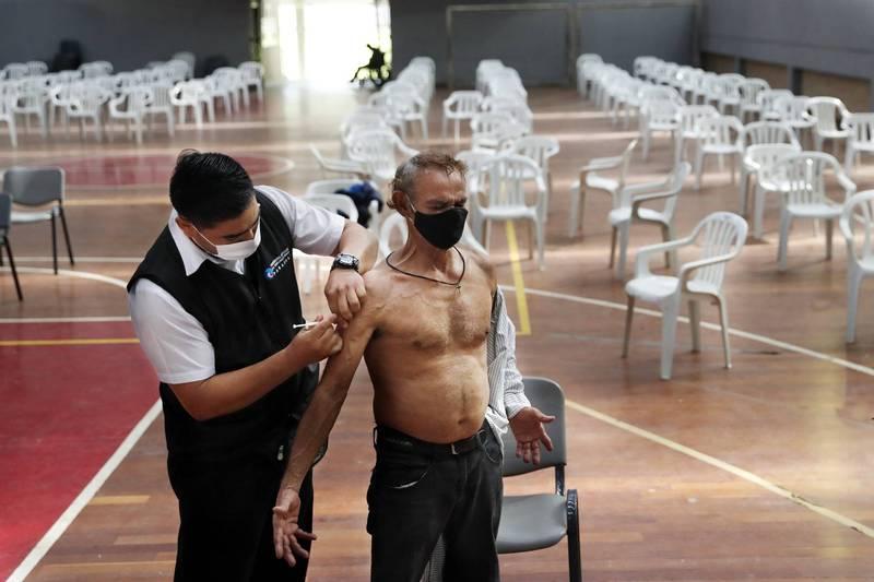世界衛生組織表示,全世界至少70%的人都接種了疫苗,武漢肺炎疫情才會結束。圖為巴拉圭醫療人員27日為一名73歲男子接種疫苗的畫面。(美聯社)