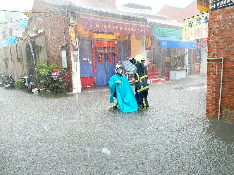 A firefighter gives a pedestrian directions amid flooding in Changhua County's Lukang Old Street yesterday. Photo: provided by the Changhua County Fire Deparment via CNA
