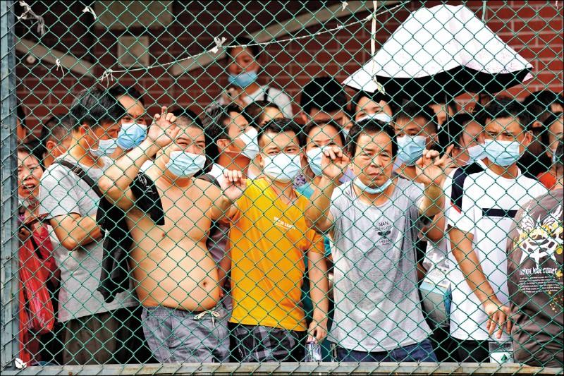 中國廣東省廣州市近期爆發多起感染印度變種病毒株的確診案例,三十日不少民眾在篩檢站接受武肺篩檢。(美聯社)
