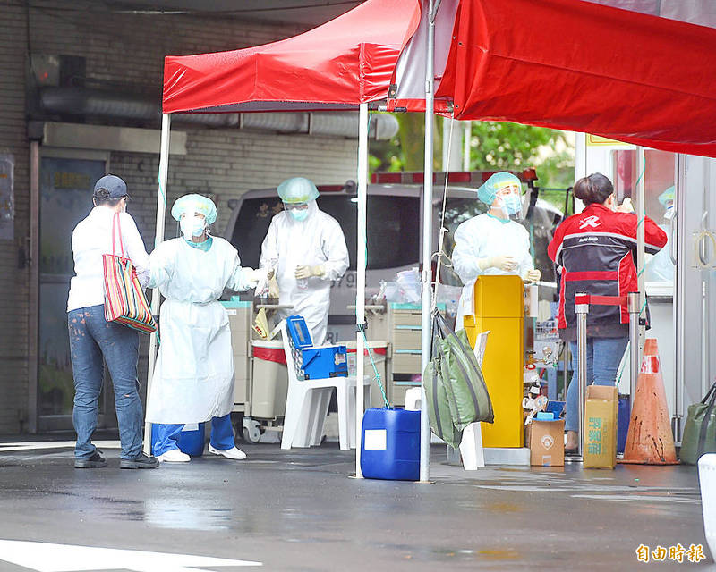 Medical staff operate a COVID-19 rapid screening station outside Taipei City Hospital's Zhongxiao branch yesterday. Photo: Fang Pin-chao, Taipei Times