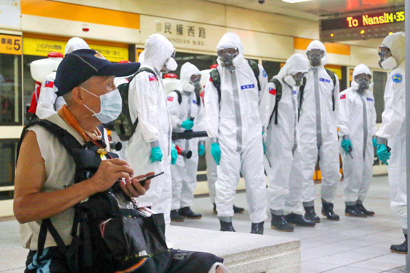 Army Chemical Corps personnel yesterday assemble on an MRT platform in Taipei to carry out COVID-19 disinfection work. Photo: CNA