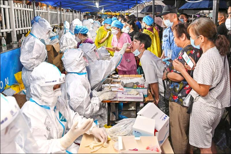 中國廣東省廣州市因疫情升溫,擴大採檢規模,全副武裝的醫護人員五月三十日為民眾進行武漢肺炎採檢。(路透)