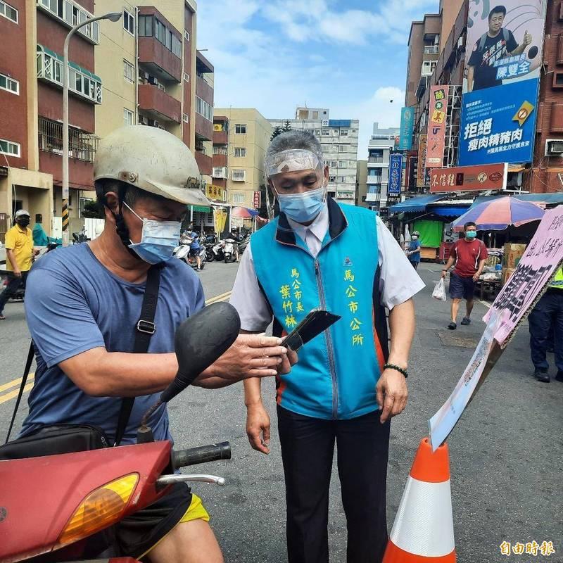 馬公市長葉竹林指導民眾,如何使用手機掃描QRO。(記者劉禹慶攝)