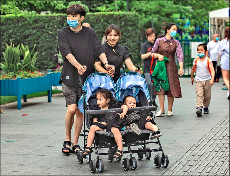 中國政府二○一五年秋天改行「全面二孩」生育政策,上月卅一日確定升級「三孩」。圖為中國上海市一對夫婦在一日兒童節帶兩個孩子上街。 (歐新社)