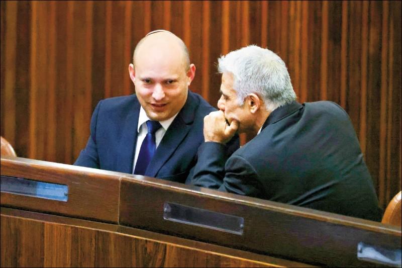 以色列「右傾黨」黨魁班奈特(左)二日在國會特別會議上,與「未來黨」黨魁拉皮德(右)談話。(美聯社)