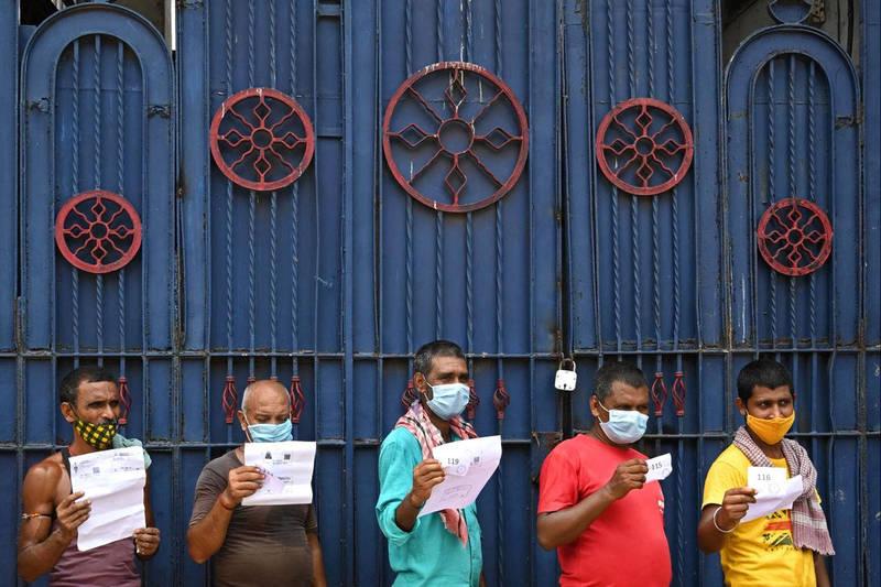 印度加爾各答的勞工3日拿著文件,排隊等待接種第一劑阿斯特捷利康(AstraZeneca)授權印度血清研究所生產的Covishield疫苗。(法新社)