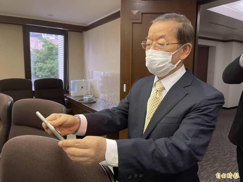駐日代表謝長廷以手機觀看疫苗專機順利降落,表示「總算安心了」。(記者林翠儀攝)