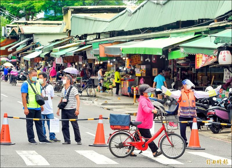 新北市傳統市場實施人流管制,三重區的力行路市場,由警方及工作人員管制車輛進入,避免採買人潮群聚。 (記者劉信德攝)