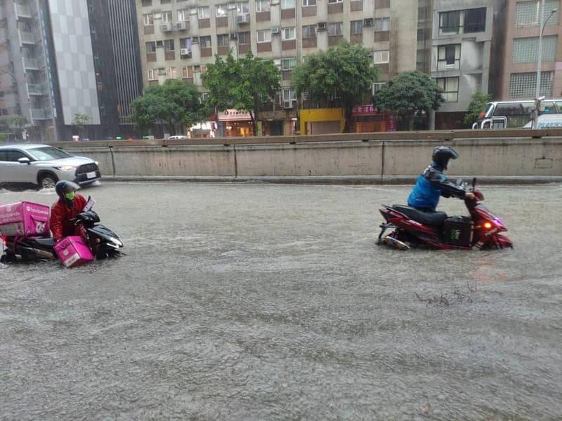 台北市午後下起暴雨,多處地區皆傳出淹水災情,有外送員騎機車經過,機車直接泡在水中,只好下車用牽的。(圖取自臉書「外送員的奇聞怪事」)