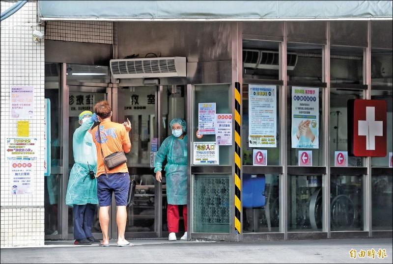 疫情未趨緩,4日台北市聯醫忠孝院區急診室外,醫護人員先對前來就診的民眾量測體溫。(記者方賓照攝)