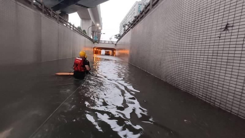 消防隊員穿著救生衣,游泳進入地下道,將受困民眾救出。(圖由讀者提供)
