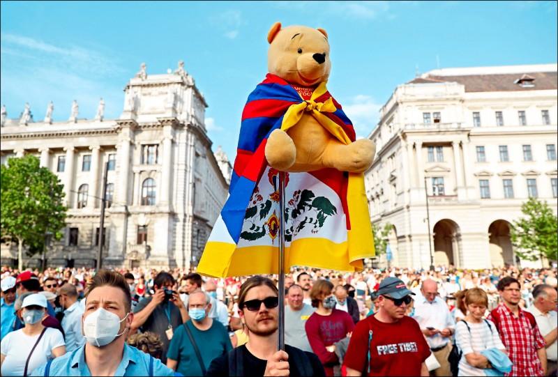 匈牙利布達佩斯居民反對中國復旦大學在當地開設海外分校的計畫,五日約有一萬人走上街頭抗議。遊行隊伍中,有人高舉暗諷中國國家主席習近平的「小熊維尼」布偶,身上還披著一面代表西藏的「雪山獅子旗」。 (路透)