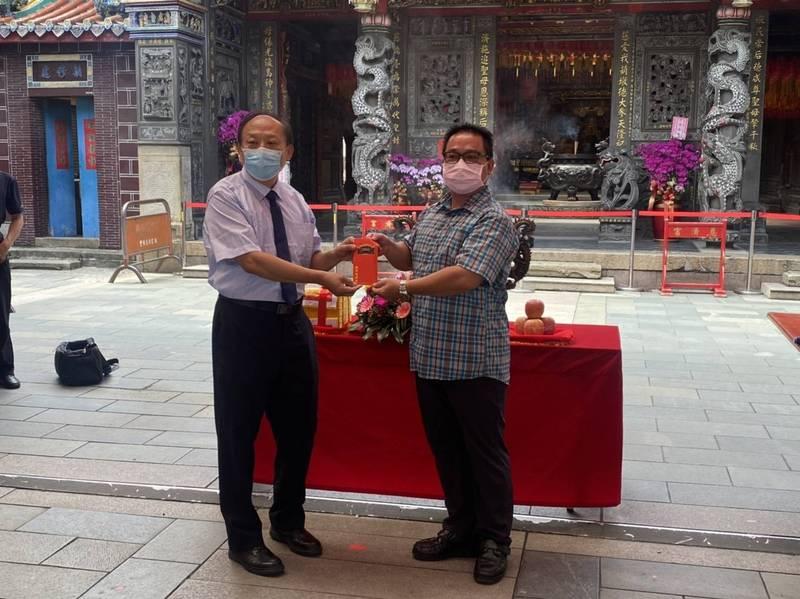 慈濟宮副主委黃國益(左)頒發獎勵金,由豐原分局偵查隊長陳俊彥(右)代表接受。(記者歐素美翻攝)