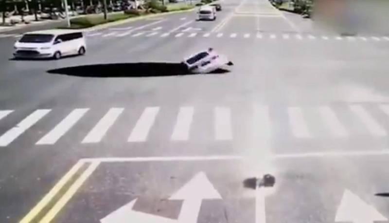 中國吉安本月5日上午一處十字路口路面突然塌陷,一台轎車未注意而摔入坑中。(擷取自微博)