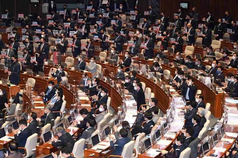南韓執政黨共同民主黨12名國會議員涉嫌炒房,目前黨中央定調一律要求退黨處理。圖下方處為共同民主黨議員,上方為反對黨舉牌抗議。(歐新社)