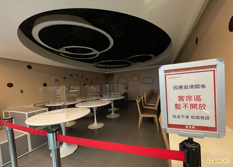 包括第一航廈、第二航廈的美食街,均已貼上「餐飲一律外帶、禁止內用」的告示,業者也將內用區的座位全數收疊在餐桌上,並拉起紅龍線配合防疫措施。(記者劉信德攝)