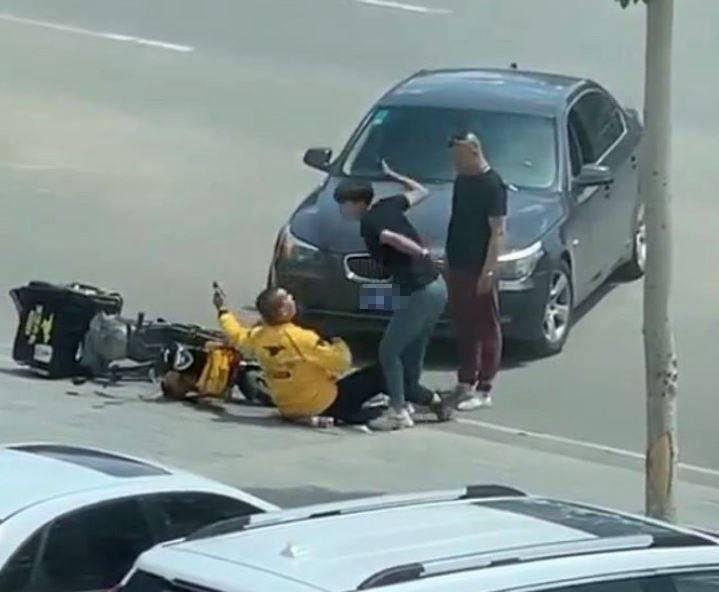 1輛黑色BMW轎車與1名騎乘機車的外送員發生碰撞,外送員倒地後竟遭BMW女乘客當街暴打。(圖取自微博)