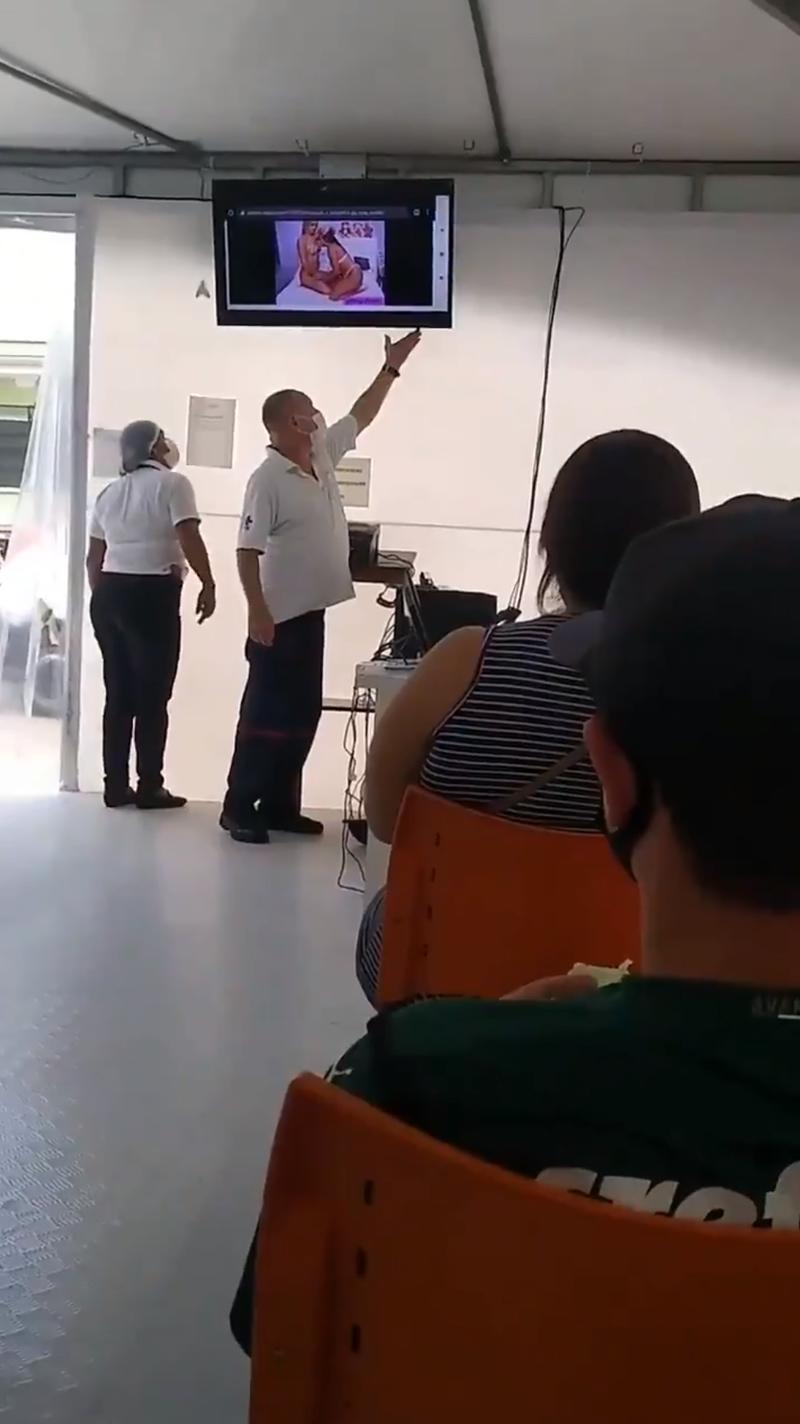 推特用戶「JaviHIVer」爆料,本月7日他陪同外公去哥斯大黎加一處接種站施打疫苗時,等候區的電視竟突然播出「女女AV」(圖翻攝自JaviHIVer推特)