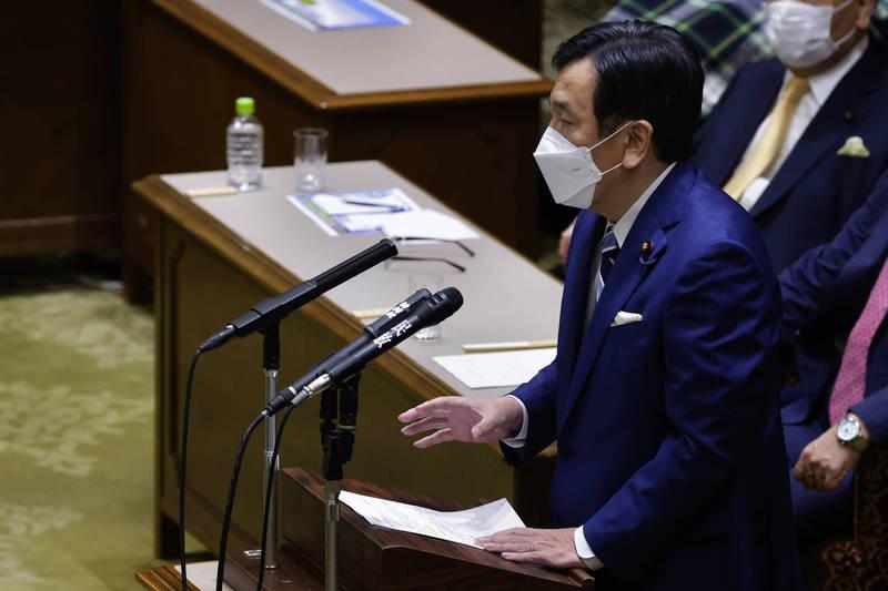 日本立憲民主黨黨魁枝野幸男日前針對「東奧是否舉辦」質詢日本首相菅義偉。(彭博)