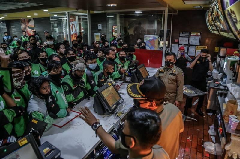 印尼麥當勞週三開賣BTS聯名套餐,掀起一波搶購熱潮,現場擠滿前來取餐的外送員。(法新社)
