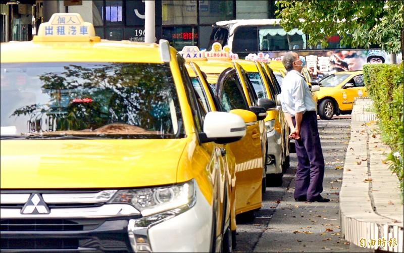 疫情衝擊,計程車排長龍苦等不到上車的旅客,運將無奈仰頭長嘆。(記者羅沛德攝)
