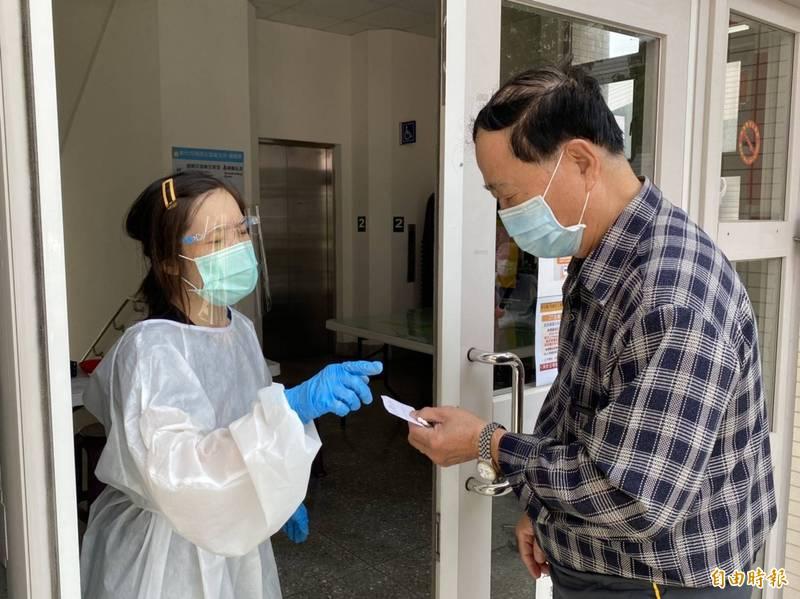 衛生所人員拿出紙條,請要預約民眾打電話預約接種疫苗。(記者張聰秋攝)