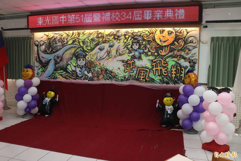 美術班潘勁瑞以逆風高飛為主題,在學校內的玻璃白板,用擦擦筆作畫,當作畢業典禮的舞台。(記者林敬倫攝)