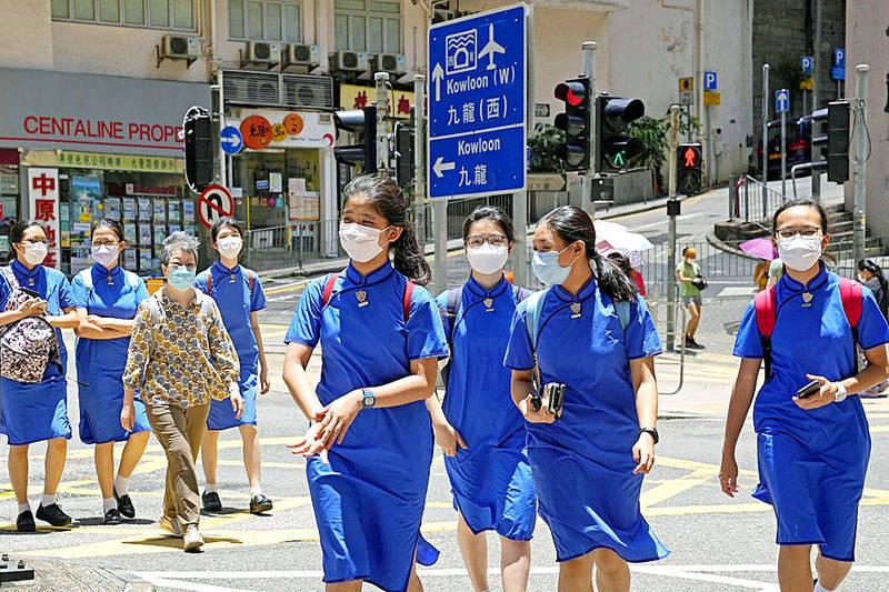 Students wearing masks cross a street in Hong Kong on Thursday. Photo: AP
