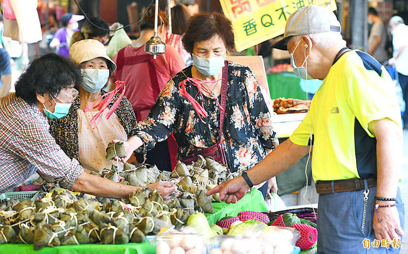 Shoppers at Taipei's Wuxing Street traditional market buy zongzi — glutinous rice dumplings in bamboo leaves — which are traditionally eaten during the Dragon Boat Festival. Photo: Liao Chen-huei, Taipei Times