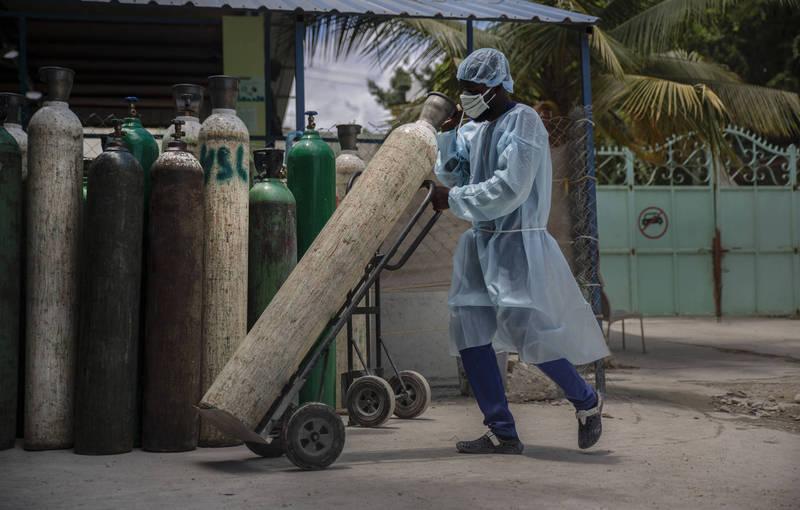 海地疫情陡然爆發,卻連1劑疫苗都還沒開始打。圖為海地醫護人員運送氧氣罐。(美聯社)