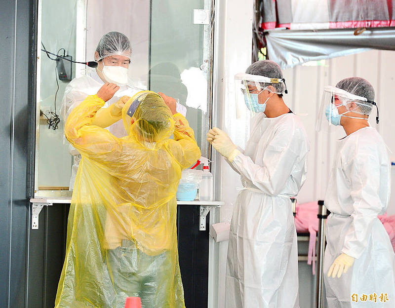 Healthcare workers collect COVID-19 test samples from a person at a test station in New Taipei City's Banciao District yesterday. Photo: Wang Yi-sung, Taipei Times