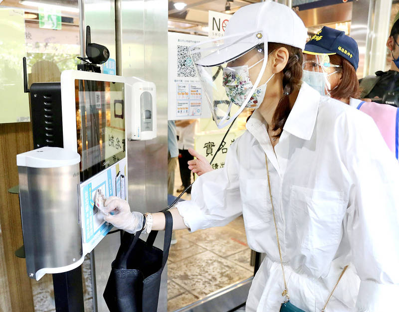 A woman swipes her identity card at the entrance of Nanmen Market in Taipei yesterday. The government has implemented staggered admission to crowded shopping venues according to the last digit of people's identity or resident certificate numbers.  Photo: CNA