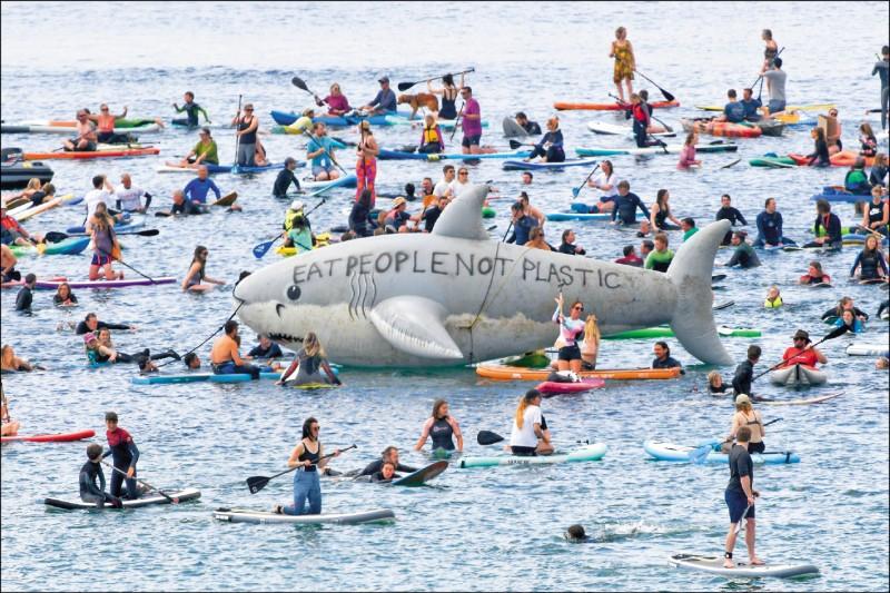 G7領袖在英國康瓦爾郡海濱度假勝地卡比斯灣聚首之際,抗議者在同郡法爾茂斯地區的海灘聚集,並在海中立起寫有「吃人不吃塑膠」的大型鯊魚氣球,促G7領袖為環保做出更多貢獻。(路透)