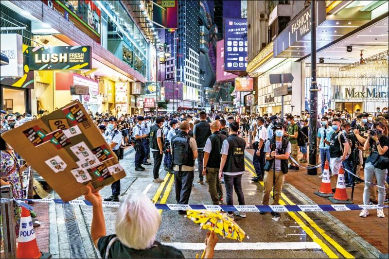 在香港,網路上有人號召民眾晚上七點「街頭見」,港警出動大批員警戒備,晚間旺角一帶有零星人群聚集,數十人遭盤查,兩人被捕。(彭博)