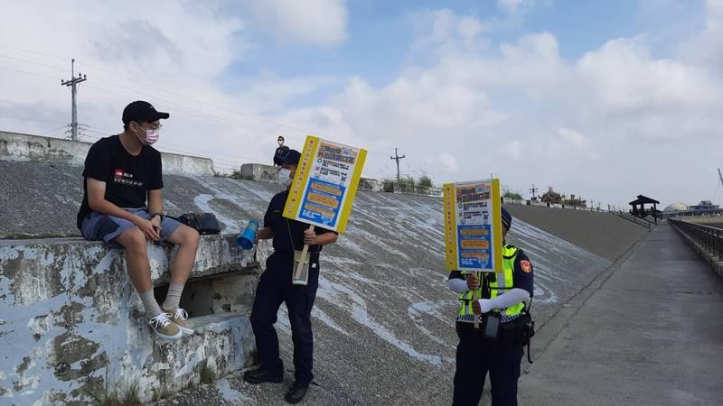 清水分局員警高舉標語及大聲公,到高美濕地向民眾宣導防疫。(記者歐素美翻攝)