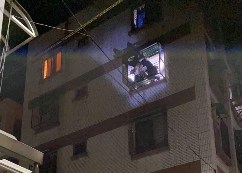 消防隊員將倒栽蔥卡在窗台的王男救回屋內(民眾提供)