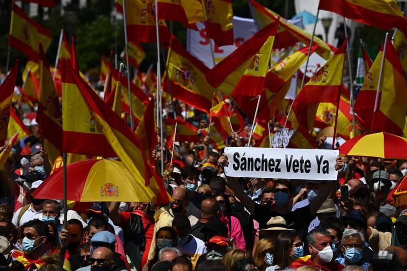 成千上萬民眾週日在馬德里上街抗議政府計畫特赦加泰獨派,有民眾舉標語要總理桑切斯下台。(法新社)