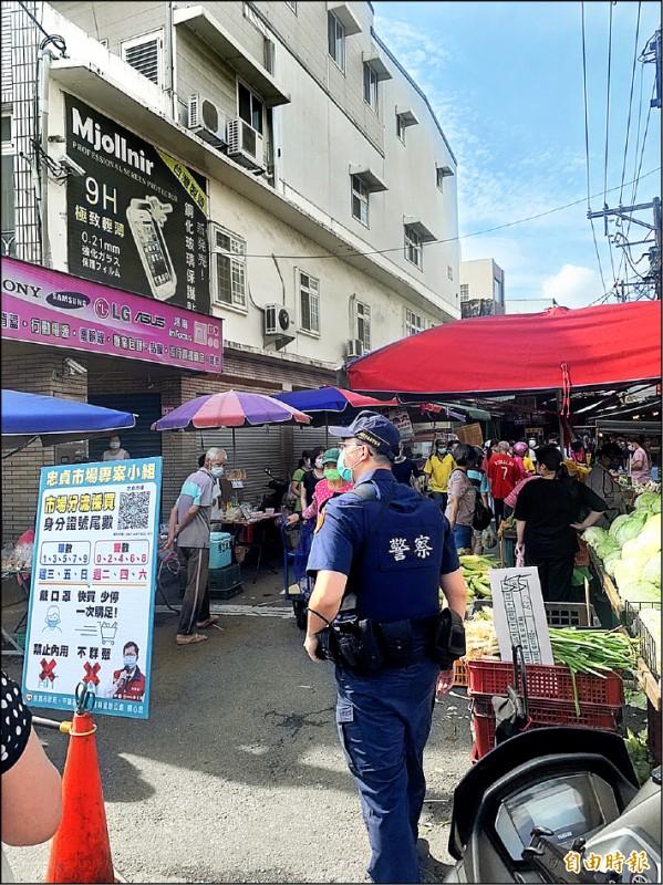 端午連假,忠貞市場人潮湧現,員警疏導交通也協助引導民眾快買、少停避免群聚。(記者李容萍攝)